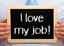 I love my job - Manager with chalkboard. I love my job - Manager holding chalkboard with text in his hands royalty free stock photo