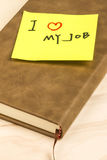 I love my job note and notebook. Close up of a post-it note saying I love my job and a notebook on wooden background Stock Photos