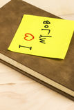 I love my job note and notebook. Close up of a post-it note saying I love my job and a notebook on wooden background Royalty Free Stock Image