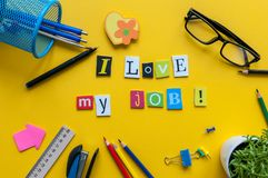 I love my job word written by carved letters on yellow home workspace with office supplies Stock Photo