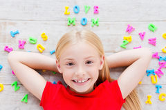 I love my mom!. Top view of cute little girl holding hands behind head while lying on the floor with plastic colorful letters laying around her Royalty Free Stock Photos