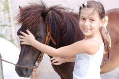 I love my pony. Girl holds her little pony, so cute that it looks like a toy Royalty Free Stock Photo