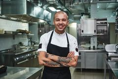 I love my work Cheerful young chef in apron keeping tattooed arms crossed and smiling while standing in a restaurant. Kitchen. Cooking concept royalty free stock photos