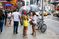 I love new york. New York City, USA - August 3, 2013:girls with umbrellas walk between the traffic and billboards time square in a rainy day royalty free stock photo