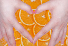 I love orange. Hands shaped in heart, fresh oranges in background Royalty Free Stock Photos