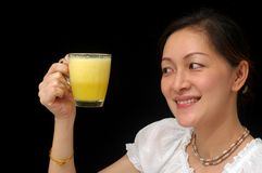 I love orange juice. Chinese young lady holding a cup of orange juice and smiling Royalty Free Stock Photo
