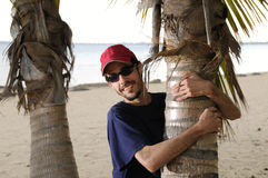I love this palm. Man embracing coconut palm tree trunk on a beach Royalty Free Stock Image