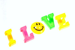 I love phrase with smile button on white. Phrase I love from plastic letters and smile button isolated on white Royalty Free Stock Photo