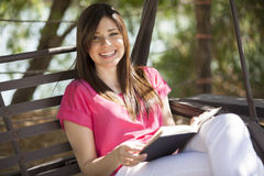 I love reading. Happy young woman reading a book and relaxing outdoors Stock Image