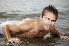 I love salt water. Young man posing on Italian bech in water and relaxing in summer sun royalty free stock images