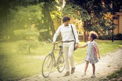 I love school days. African American father and his daughter walking trough park and talking stock images