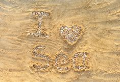 I love sea. Letters and heart made from small stones and seashells on sea sand. I love sea. Letters and heart made from small stones and seashells on the sea stock photography
