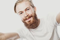 I love selfie! bearded man holding smartphone and making selfie and smiling while standing against white background. stock photography