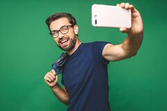 Free I Love Selfie! Handsome Young Man In Shirt Holding Camera And Making Selfie And Smiling While Standing Against Green Background Royalty Free Stock Photo - 186052855