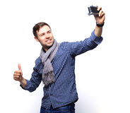 I love selfie! Handsome young man in shirt holding camera. And making selfie and smiling while standing against white background Royalty Free Stock Photo