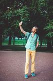 I love selfie. Outdoor summer lifestyle portrait of young bearded man holding camera and making . Smiling hipster guy in shirt wal Royalty Free Stock Photography