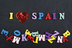 I love SPANISH word on black board background composed from colorful abc alphabet block wooden letters, copy space for. SPANISH word on black board background stock photo