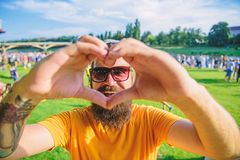 I love summer holiday festival.Hipster happy celebrate event picnic fest festival. Man bearded in front of crowd people. Show heart gesture riverside background royalty free stock photography