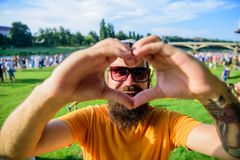 I love summer holiday festival.Hipster happy celebrate event picnic fest festival. Man bearded in front of crowd people. Show heart gesture riverside background royalty free stock image