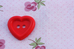 I love to sew. Red heart button on a background of cloth stock photos