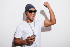 I love this track!. Happy young African man in headphones holding his music player and gesturing while standing against white background Stock Image