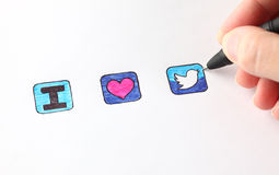 I love Twitter. Tambov, Russian Federation - December 16, 2012: Woman's hand with ballpoint pen draw signs - I, heart and Twitter's icon. Studio shot Stock Photography