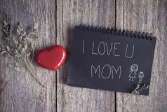 I love u mom message note with flower. On old wooden background Royalty Free Stock Image