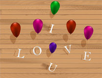 I love u sign hanging on colorful ballons on wooden texture. I love u sign hanging on colorful ballons Royalty Free Stock Images