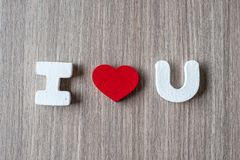 I Love U word of wooden alphabet letters with red heart shape on table background. Romance, Romantic and Valentine's day royalty free stock photography
