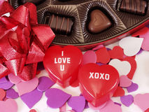 I Love U XOXO Hearts. Multi colored heart cut outs spilled around a heart shaped box of chocolate candy. A shiny red bow and 2 plastic heart boxes saying I love Stock Photos