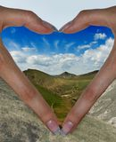 I love this world. Fingers in the form of heart against landscape royalty free stock image