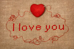 I love you. Valentine embroidery 'I love you' with knit ball in a form of a heart pierced with needle royalty free stock photo