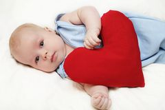 I love you. The lying baby embraces heart royalty free stock photography
