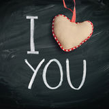 I Love You. Handwritten message on a chalkboard with a rustic needlework heart used as a symbol of love in this Valentines message Stock Photography
