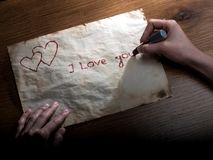 I Love you. Girl writing a valentine to his beloved lipstick on the old paper royalty free stock photos
