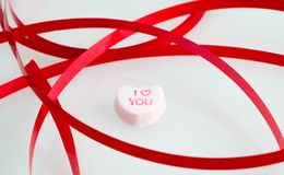 I love you. Red ribbons frame a candy heart Stock Photo