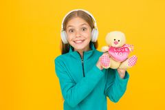 I love you with all my heart. Happy girl celebrate love. Little child wear earphones with teddy bear. Love you