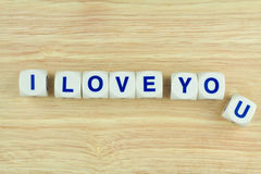 I LOVE YOU Alphabet Cubes. Blue Alphabets on White Cube Blocks say I LOVE YOU on the Wooden Surface Background Royalty Free Stock Image