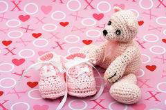I Love You Bear. A pink handmade teddy bear and baby booties on a love background, I love you bear Stock Images