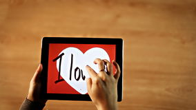 I love you calligraphy. Female writing bold inside white heart on tablet stock video