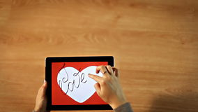 I love you calligraphy. Female writing thin inside white heart on tablet stock video footage