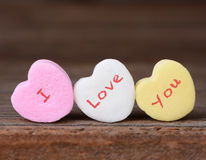 I Love You on Candy Hearts. Closeup of the words I Love You spelled out on candy hearts. Three hearts on a rustic wood background. Great for Valentine's Day stock images
