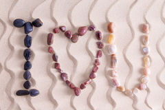 I Love You in colorful stones on golden beach sand Stock Images