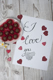 I love you concept with glittered hearts. I love you concept with glittered red hearts photographed on white wood background Royalty Free Stock Image