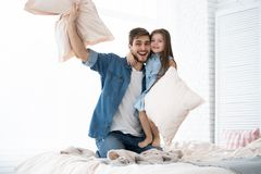 Happy father and daughter playing pillow fight in bed at morning. I love you, dad! Happy father and daughter playing pillow fight in bed stock photography