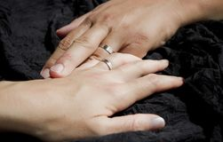I love you darling. Two hands holding wedding rings, touching each other, on black background Royalty Free Stock Image