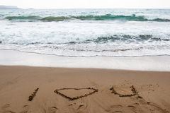 I love you drawn in the sand of a Greek beach with turquoise water royalty free stock images