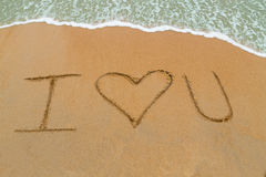 I Love You drawn on sandy beach with wave approaching Royalty Free Stock Photo