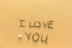 I Love You - hand-written on the sand in line of the sea surf. Abstract. Stock Photos