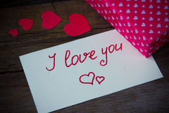I love you handwritten on white paper and hearted gift box Royalty Free Stock Photo